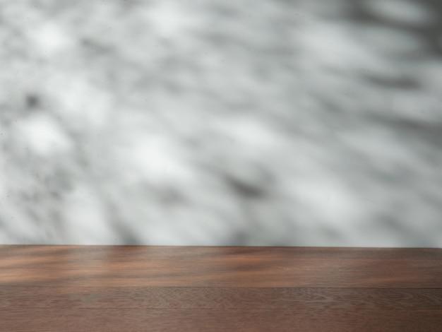 Mesa vacía sobre fondo de pared con sombras naturales