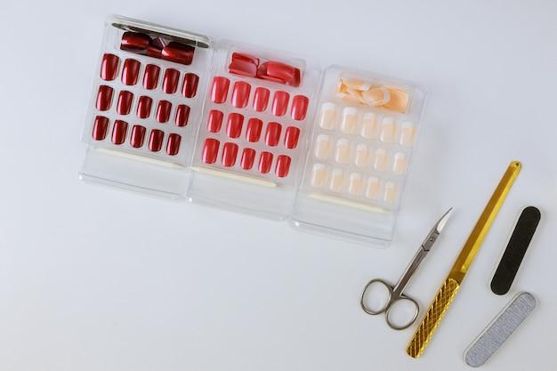 Mesa con él varios paleta de diseños de uñas de diferentes colores sobre una mesa de luz.