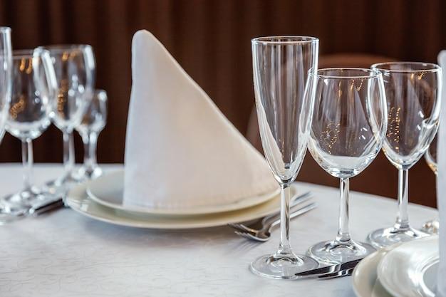 Mesa con vasos y servilletas para la cena en el restaurante.