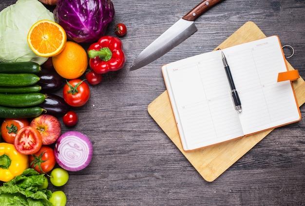 Mesa con verduras, un cuchillo y un cuaderno
