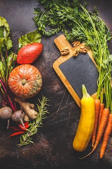 Mesa de verduras de otoño. calabaza, calabacín, batatas, zanahorias y remolachas en la mesa oscura.