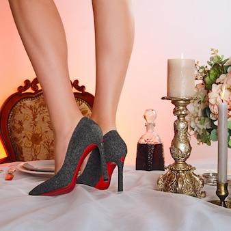 Mesa con vino y piernas femeninas en zapatos de tacón alto en la parte superior.
