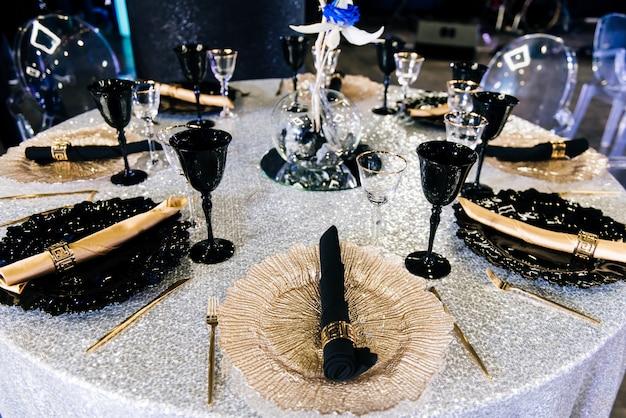 Mesas establecidas para una fiesta de evento o recepción de boda. cena elegante de lujo en un restaurante. vasos y platos negros y dorados.