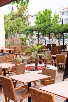 Mesas de madera de café para unas vacaciones de relax con macetas de plástico con palmeras