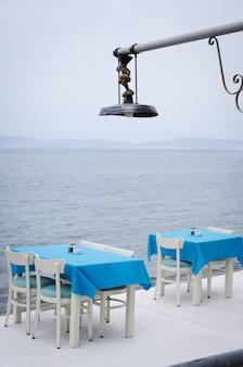 Mesas y sillas de mimbre en la terraza de una acogedora cafetería de verano con vistas al mar.