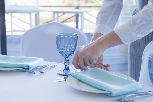 El mesero del restaurante sirve una mesa para una celebración de boda, primer plano
