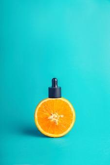 Metáfora, una botella con suero, mantequilla en una naranja. el concepto de vitamina c en cosmética y aromaterapia.