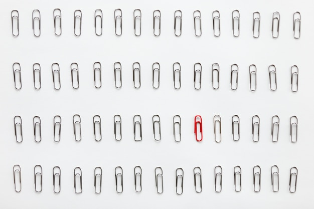 Metal clips en filas, uno rojo diferente de los demás