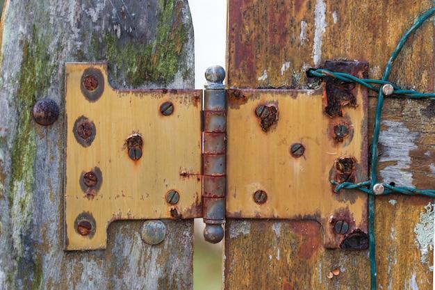 Uñas de metal, pintura sucia y despojada en la puerta de madera roja marrón y aldaba oxidada