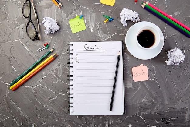 Metas como memo en el cuaderno con idea, papel arrugado, taza de café