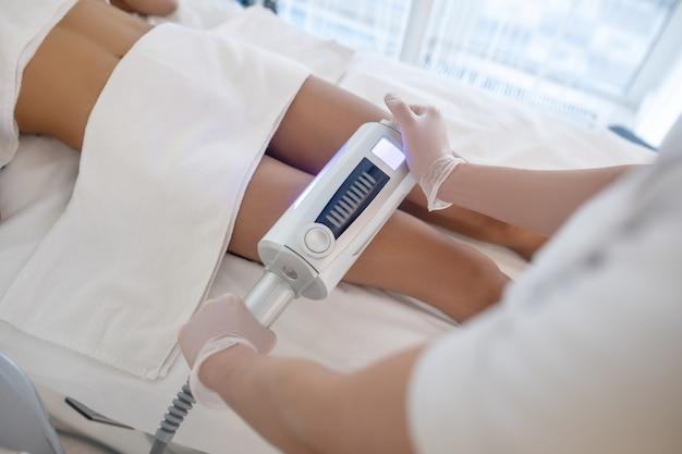 Método de adelgazamiento. manos de los médicos sosteniendo un aparato moderno sobre la pierna del paciente realizando un procedimiento de cuidado corporal