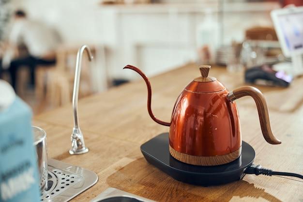 Método alternativo de hacer café mediante un filtro de embudo, accesorios para bebidas de café en una mesa de madera.