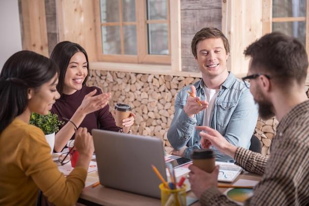 Método de lluvia de ideas. gente alegre, agradable y positiva que se sienta a la mesa e intercambia sus ideas mientras trabaja en proyectos comunes.