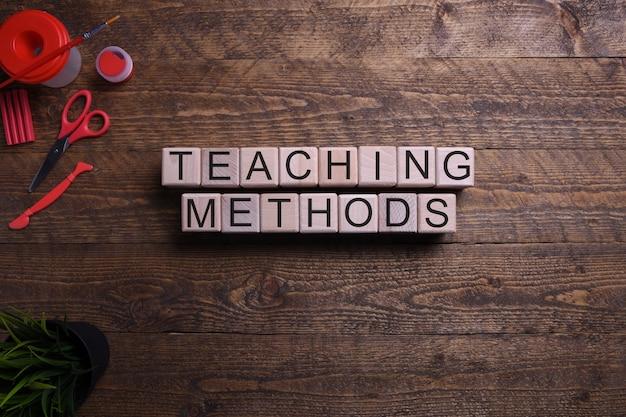 Métodos de enseñanza de palabras en cubos de madera, bloques sobre el tema de la educación, el desarrollo y la formación en una mesa de madera. vista superior.