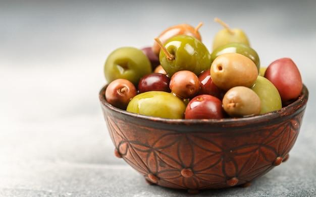 Mezcla de aceitunas marinadas (verde y morado) en un tazón de cerámica. copia espacio