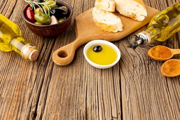 Mezcla de aceitunas de pan de alto ángulo y botellas de aceite
