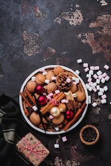 Mezcla de avellanas y nueces crudas saludables, palitos de canela, anís, vainilla, chocolate y juguetes navideños en un plato de cerámica sobre una superficie de hormigón marrón