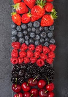 Mezcla de bayas frescas de verano orgánico en tablero de mármol negro sobre fondo oscuro de la mesa de la cocina.