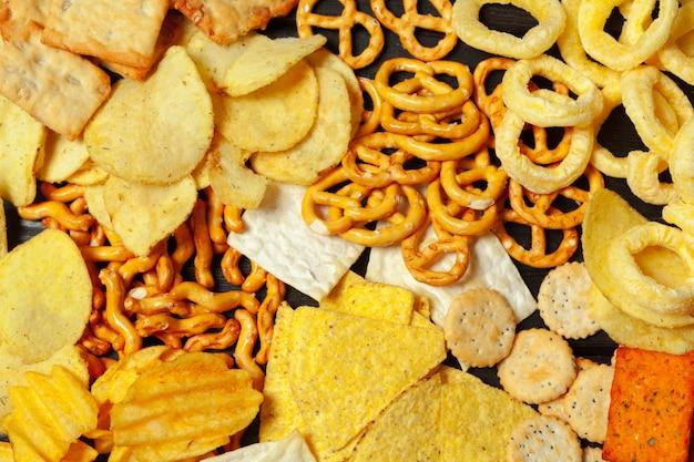 Mezcla de bocadillos: pretzels, galletas, papas fritas y nachos sobre la mesa.