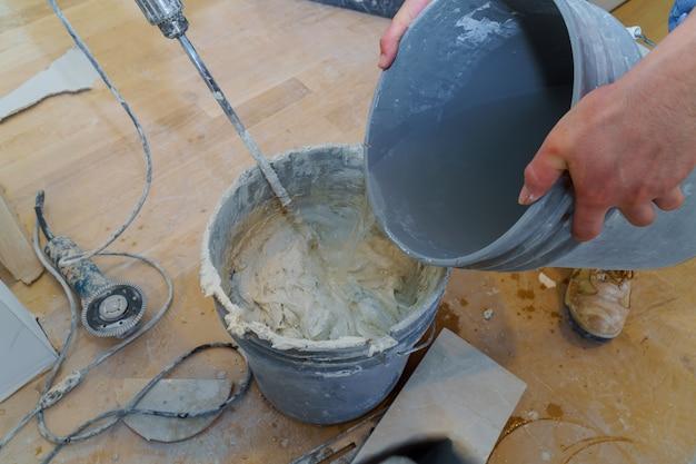Mezcla de cemento adhesivo para baldosas en un cubo para colocar en mosaico utilizando un taladro eléctrico