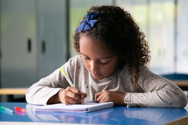 Mezcla centrada compitió niña sentada en el pupitre de la escuela y dibujo en cuaderno
