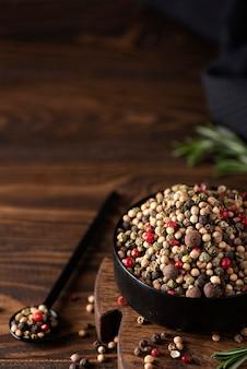 Mezcla de cinco variedades de pimienta de jamaica en un recipiente negro, primer plano