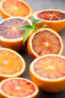 Mezcla de cítricos naranja, higos, limas sobre un fondo gris.