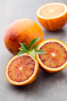 Mezcla de cítricos naranja, higos, limas sobre una mesa gris.