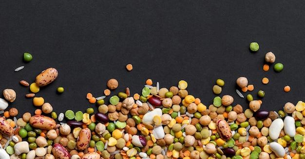 Mezcla de colores cereales y legumbres, arroz, lentejas, frijoles, garbanzo sobre fondo negro, vista superior, espacio de copia