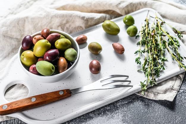 Mezcla de coloridas aceitunas saladas con un hueso. fondo gris vista superior
