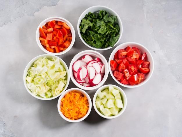 Mezcla de cuencos vegetales para ensalada o bocadillos sobre fondo gris. dieta concepto detox
