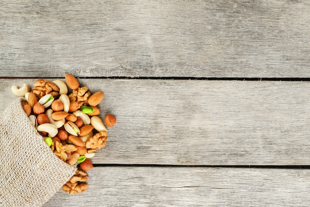 Mezcla de diferentes frutos secos en una taza de madera contra la tela de la arpillera. nueces como estructura y fondo, macro. vista superior.