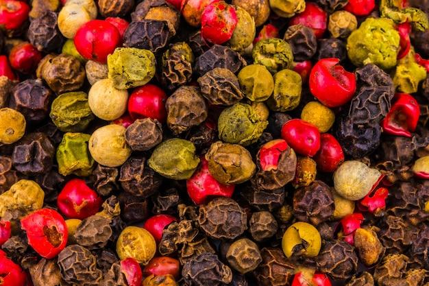 Mezcla de diferentes pimientos. granos de pimienta negra, roja y blanca - comida picante