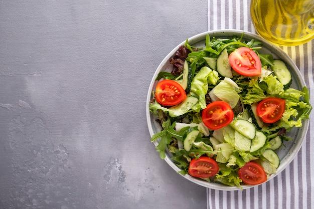 Mezcla fresca de ensaladas pepinos y tomates frescos en un plato. comida sana y dietética. vista superior.