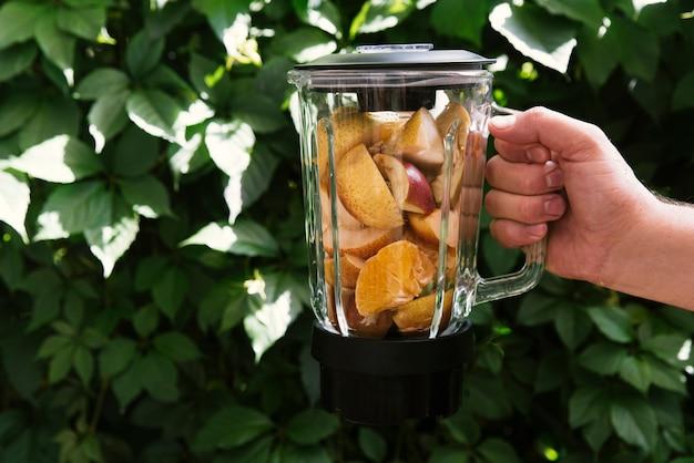 Mezcla de frutas en licuadora con fondo de hojas.