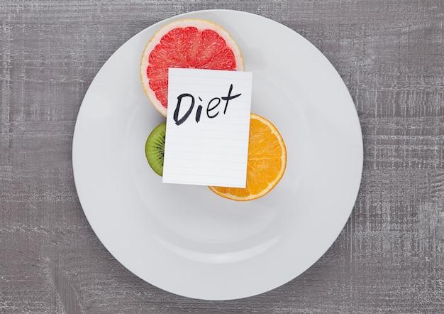 Mezcla de frutas pomelo naranja kiwi en placa con cartel de dieta en tablero de madera