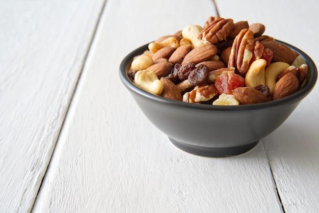 Mezcla los frutos secos y las frutas secas en el bol puesto sobre el blanco pintado de madera.