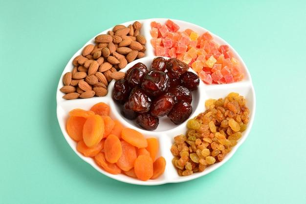 Mezcla de frutos secos y nueces en una placa blanca.