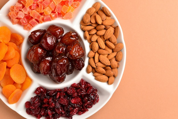 Mezcla de frutos secos y nueces en un plato blanco. albaricoque, almendra, pasas, dátiles. sobre un fondo marrón. espacio para texto o diseño.