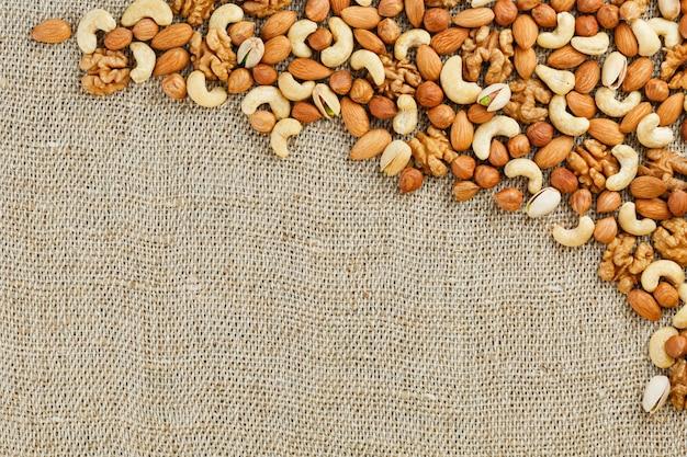 Mezcla de frutos secos sobre una arpillera de tela marrón.