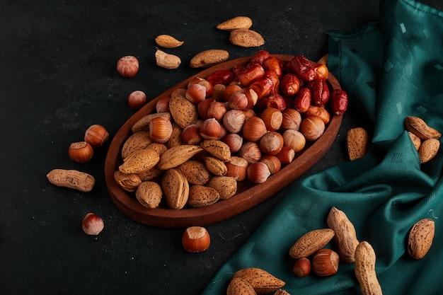 Mezcla de frutos secos en el stock de comestibles en un plato de madera sobre una toalla verde.