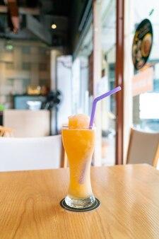 Mezcla de jugo de naranja batido de vidrio en cafetería restaurante