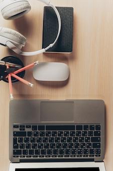 Mezcla de material de oficina y gadgets en una mesa de madera.