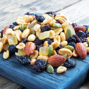 Una mezcla de nueces y frutos secos sobre una tabla de cortar de madera, fondo rústico. concepto de comida sana.