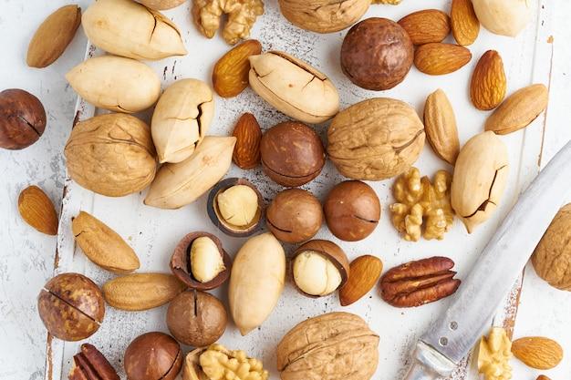 Mezcla de nueces: nuez, almendras, nueces, macadamia y cuchillo para abrir la cáscara