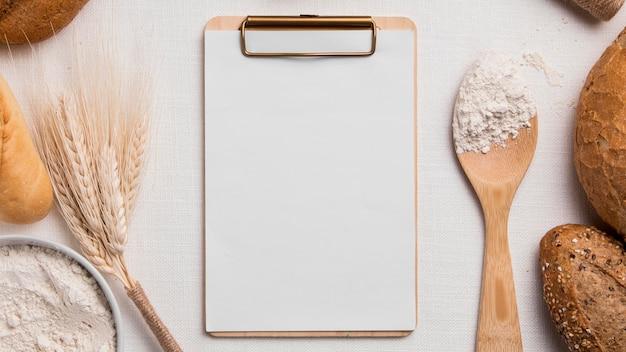 Mezcla de panes de vista superior con harina y portapapeles en blanco