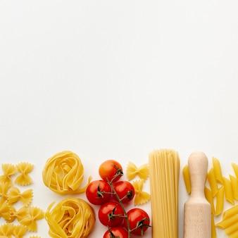 Mezcla de pasta cruda y tomates cherry con espacio de copia