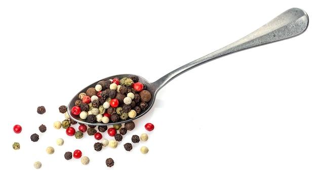 Mezcla de pimienta. diferentes granos de pimienta en cuchara aislado