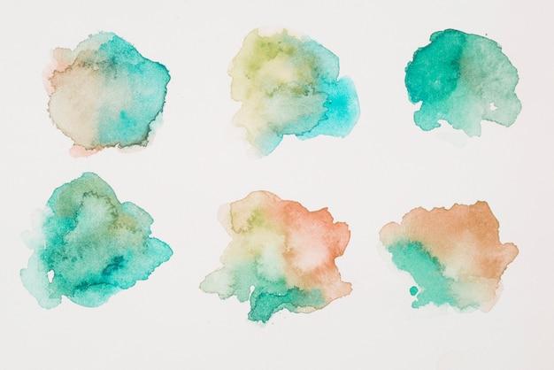 Mezcla de pinturas marrón, verde y aguamarina sobre papel blanco.