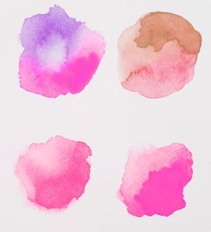 Mezcla de pinturas rosa, marrón y púrpura sobre papel blanco.